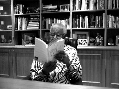 Black and white photo of Nelson Mandela at Pregs' 'favourite book reading'. Madiba is sitting at his desk, reading Pregs Govender's book, Love and Courage, A Story of Insbordination
