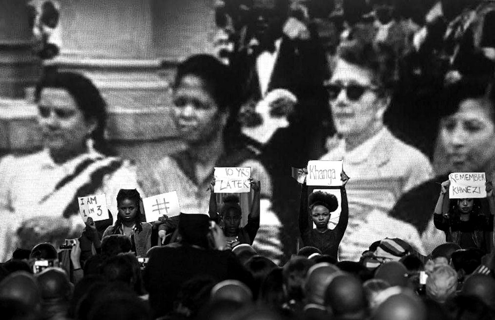Black and white digital photo collage of young women protestors silently protesting at the IEC, in solidarity with Fezeka Kuzwayo ('Khwezi'); against gender based violence and against President Zuma, placed in front of a photo of the insubordinate women leaders of the 1956 South African Women's March.