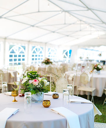 Flower decorations on a celebration table , bright white tent for party's in outdoors..jpg