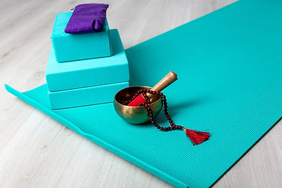 Picture of blue yoga mat with 3 blue blocks and a singing bowl