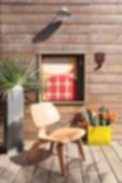 Stylisme de décoration: chaise, fleur, tableau mis en situation sur une terrasse ensoleillée