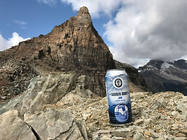 can of Sudden Draft IPA on a roacky trail in a  mountaintop landscape