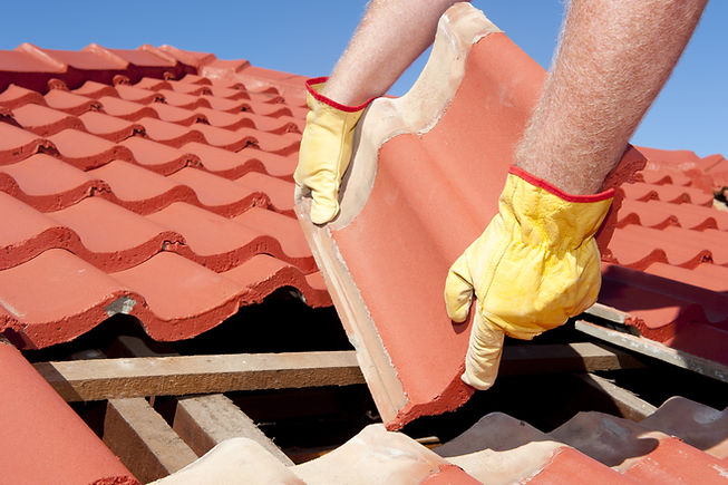 Roof repairs, worker with yellow gloves