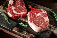 Raw rib eye steak of beef on a wooden Bo