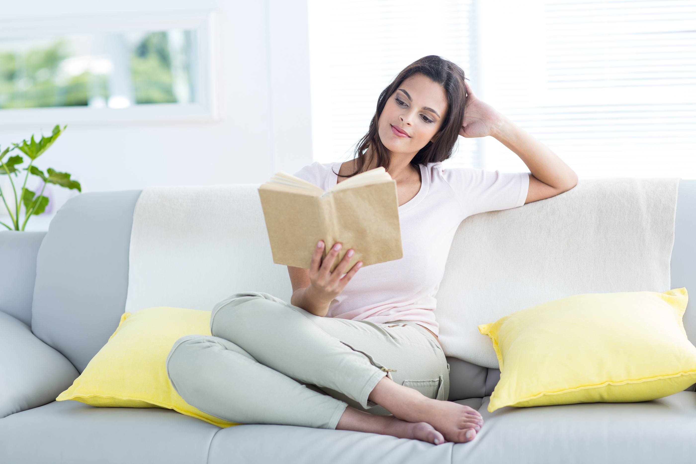 Smiling beautiful brunette relaxing and reading a book on the couch in the living room