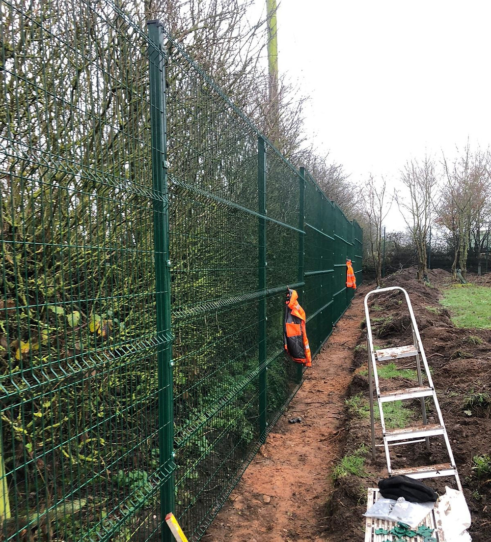 Mesh fencing being installed in a secure dog walking field.