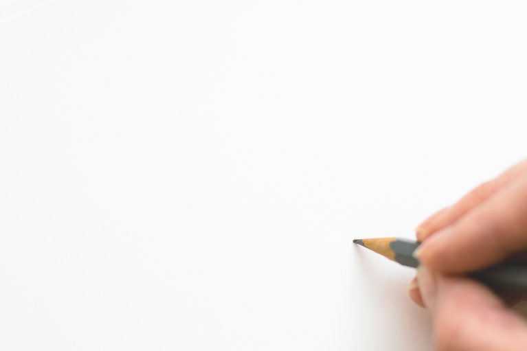 close-up-of-hand-holding-pencil-over-whi