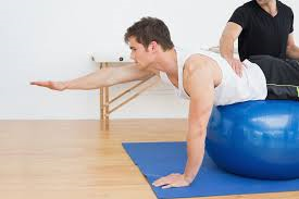 man on exercise ball reaches forward