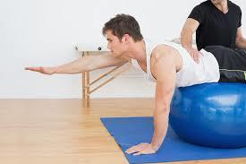 man on exercise ball reaches forward