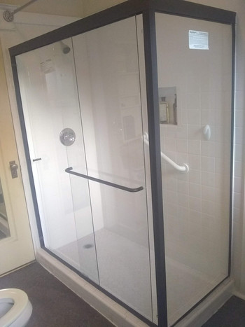Custom-sized glass allows a large shower pan without cramping the room