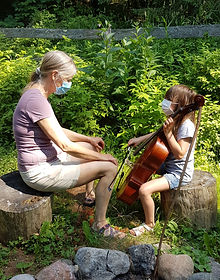 Teacher teaching little girl cello