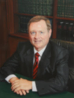 TLNPG George Bonn wearing black suit red tie sitting at his, hands folded over each other, behind him a bookcase.