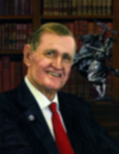 TLNPG inductee Andy Haggard seated in his office infront of a book shelf to his rightca statue of a man riding a horse