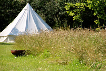 Bell Tent set up in grassy meadow camping area