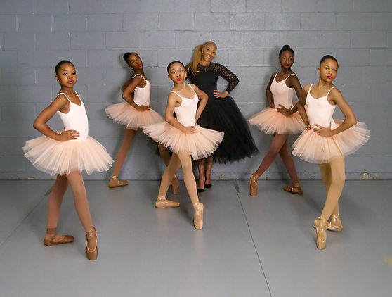 Founder and Artistic Director Paula Brown stands in a black dress behind 5 teen ballerinas in tutus.