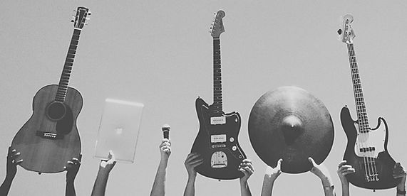 Stock image of hands holding up instruments taught at Rock University