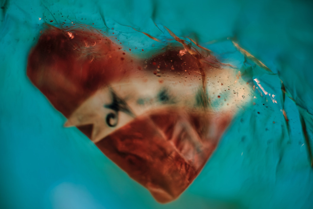 red heart submerged in what looks to be cracked glass with a blue background