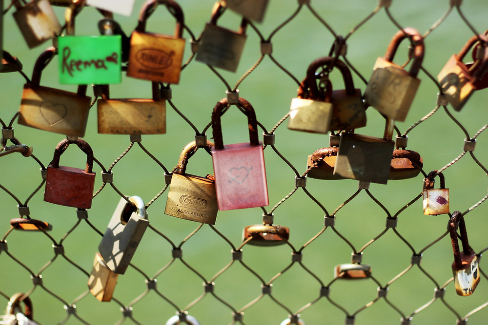 chain link fence with padlocks and wedding rings attached