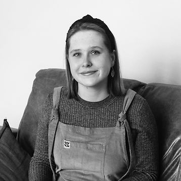 Black and white portrait photograph of Els Christensen. Smiling girl wearing Lucy and Yak dungarees, a long sleeve t shirt. She has shoulder length hair that is pushed back with a headband, also wearing leaf shaped earrings.
