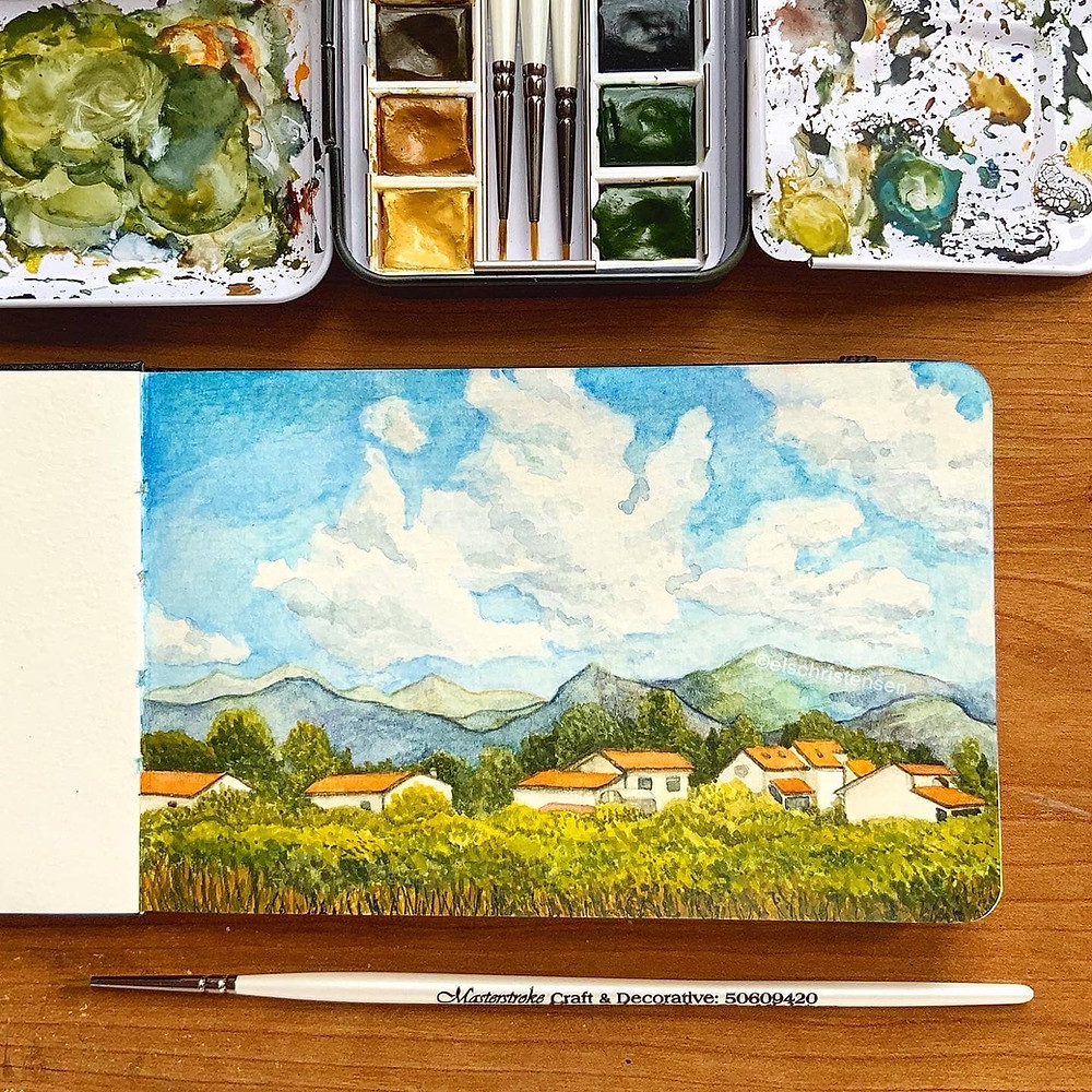 Watercolour travel sketchbook illustration. The painting is of a landscape scene of the Italian countryside, with views of the fields, Tuscan villas and mountains in the distance. Above are fluffy clouds and a blue sky. The illustration is in a sketchbook, above the sketchbook is an open tin of Winsor and Newton Professional watercolour paints. Below the sketchbook is a white ProArte miniature paintbrush.
