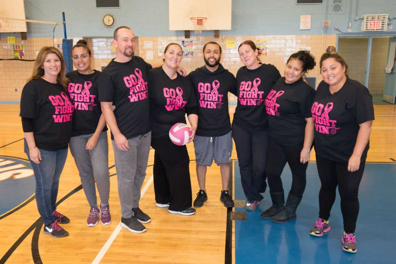 8 staff members during a charity volleyball game in the school gym.