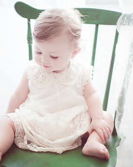 Baby Girl Sitting on a Green Chair - Baby photography in Dubai