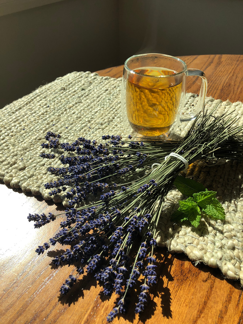 Bunches of Dried Lavender and Fresh Mint Spring with Steaming Lavender Tea in a Clear Mug