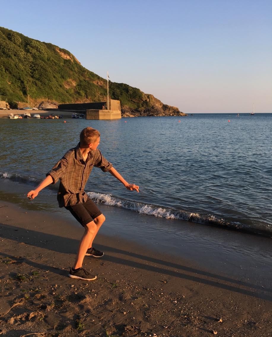 Skimming on beach at Polkerris Cornwall