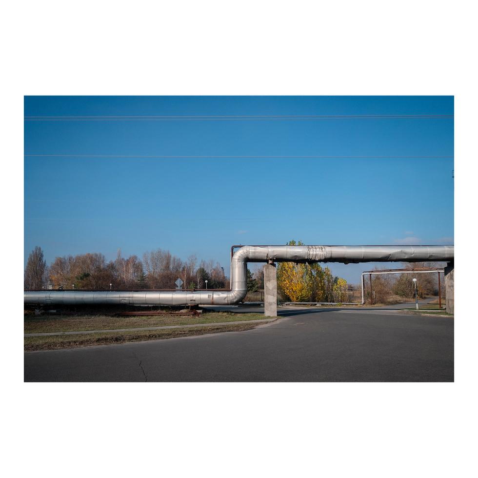 Quand arrive un carrefour, les tuyaux zigzaguent en l'air, formant un improbable réseau métallique comme si un gamin s'était amusé à relier des pailles entre elles.