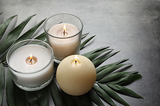Burning wax candles and tropic leaf on t