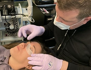 Skincare professional performing facial service to client