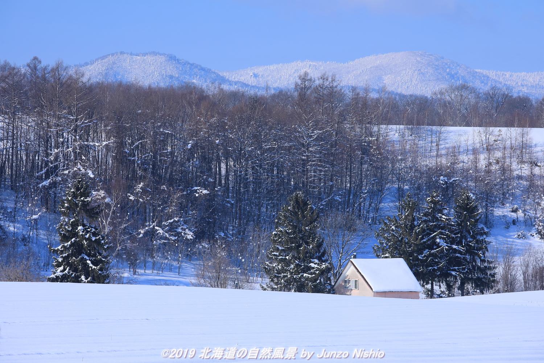 三角屋根のある冬の丘