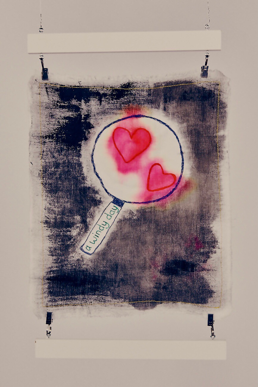 A black painted background upon which a magnifying glass has been stitched and two red hearts