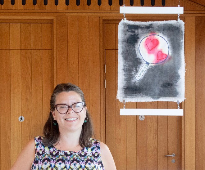 A femal artist dressed in a multicoloured top standing in front of a wooden wall with a fabric artwork hanging beside her