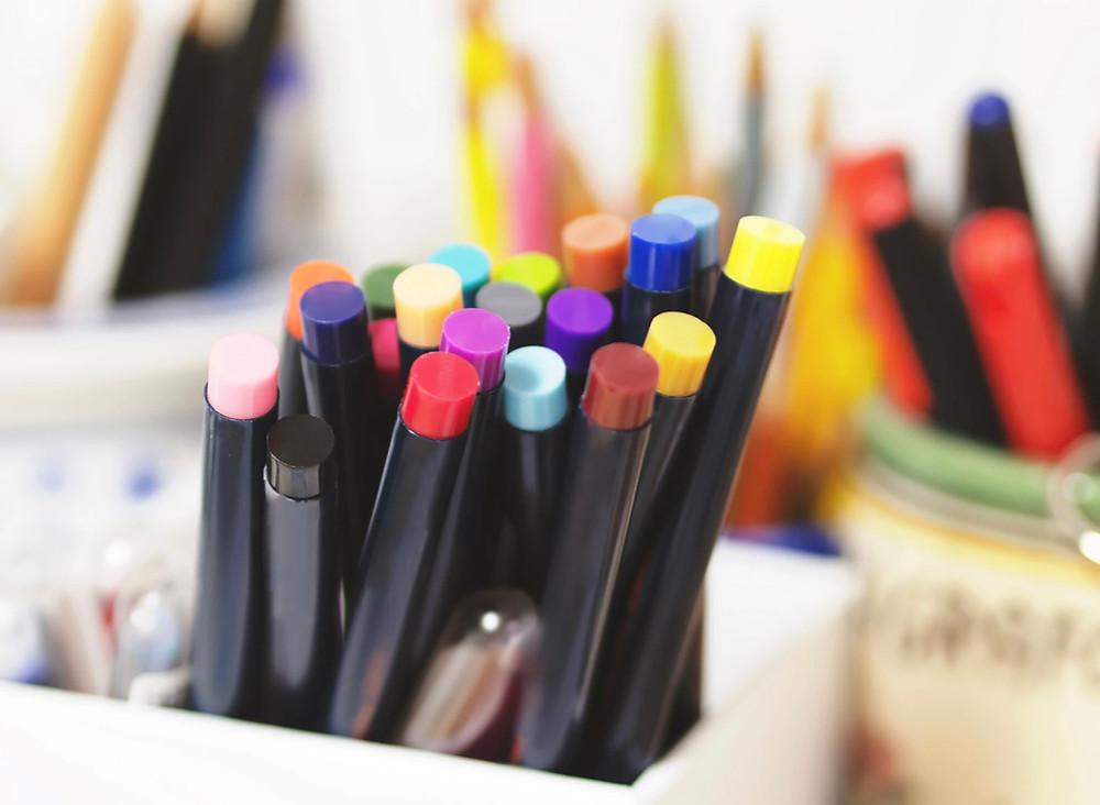Different coloured pens & pencils in a pot