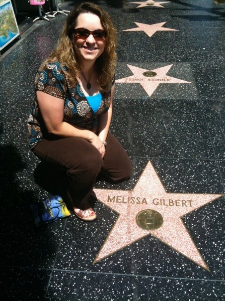 Author crouched down by Hollywood star on ground