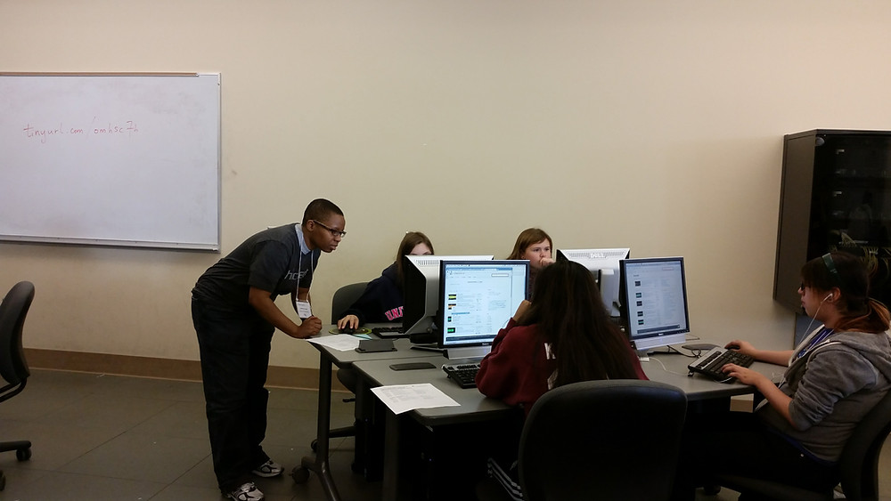 LaShana Lewis helping students during ChicTech, a girl's coding camp.