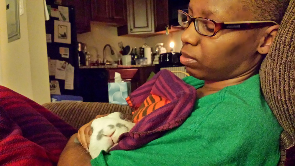 LaShana Lewis seated in a green shirt with her pet rabbit wrapped in a multi-colored blanket.