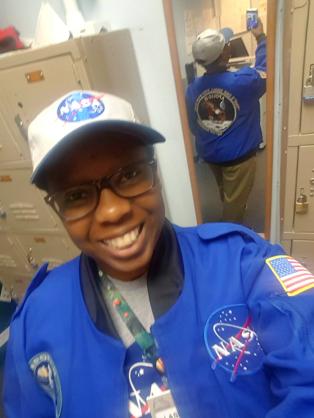 LaShana Lewis pictured wearing NASA flight jacket and baseball cap and t-shirt.  Jacket back is pictured in the mirror with the Apollo 11 mission patch.