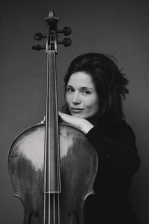 Black and white picture of a cellist. She is sitting behind the cello and leaning over it