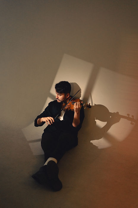 Man playing the violin with a window shadow