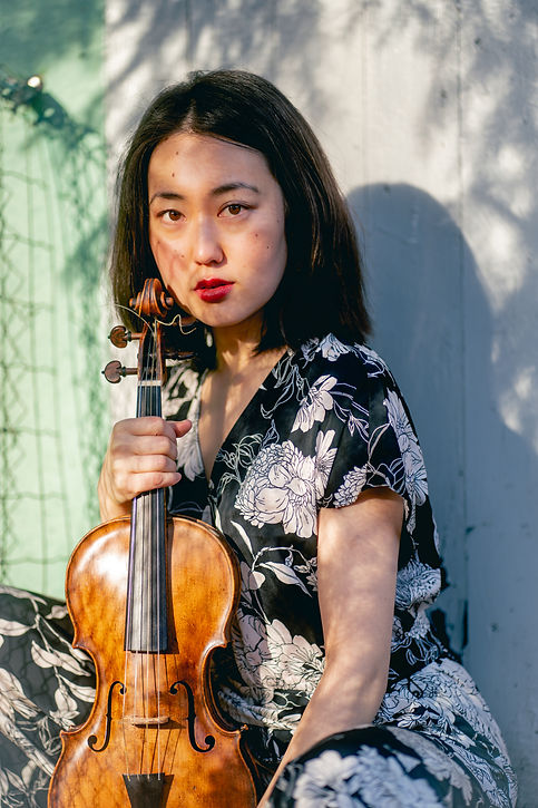 Violinist, a woman holding a violin in front a green Wall.