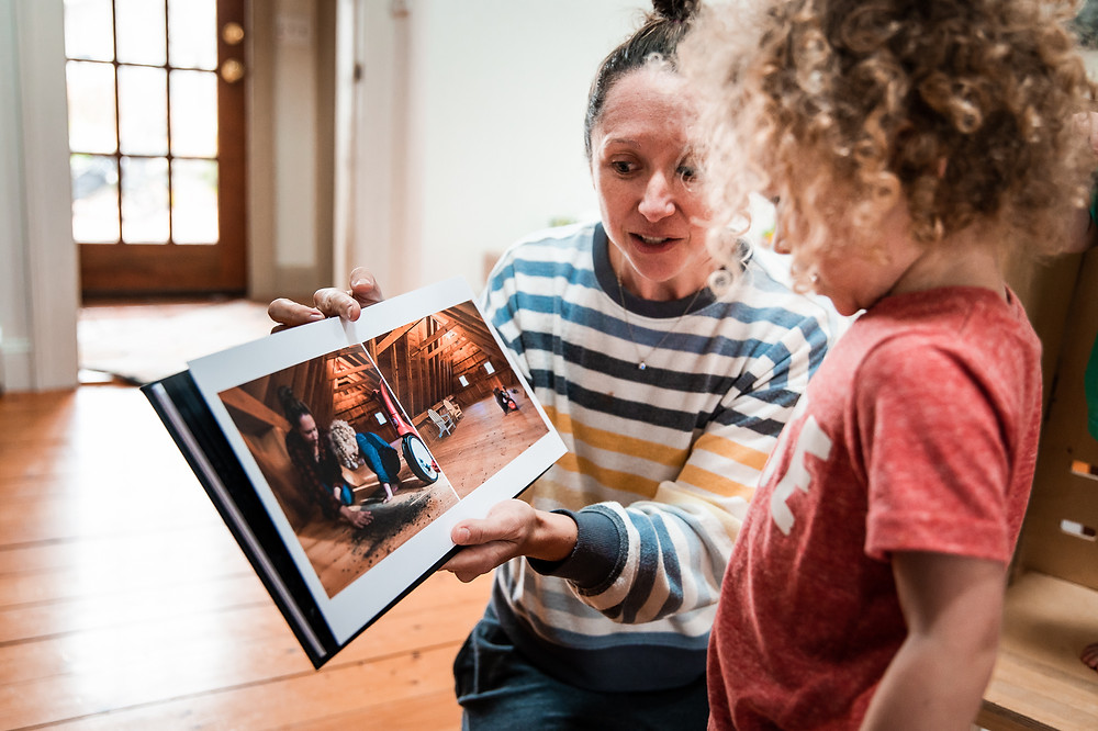 mom showing boy photo book photo album in living room