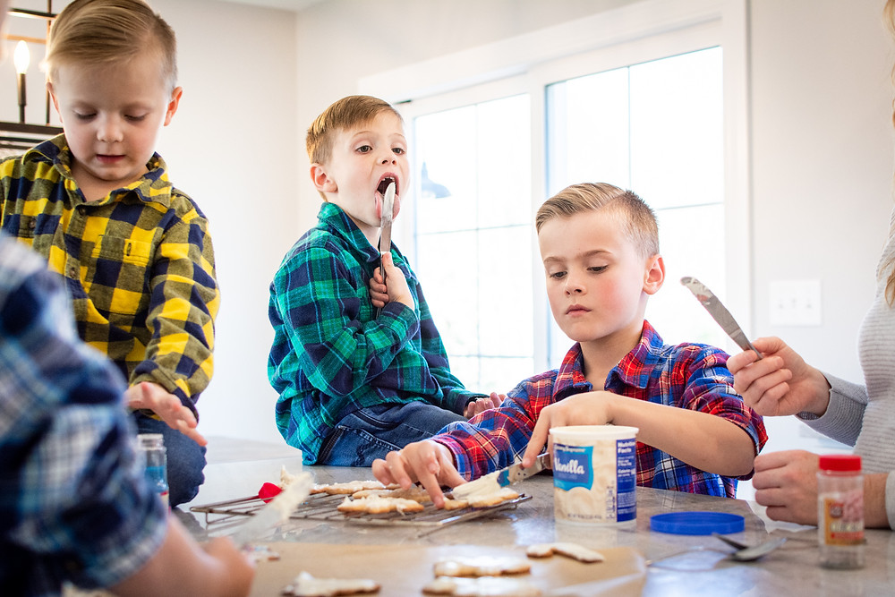 family making christmas cookies child licking frosting during family photo session baking cookies boys wearing matching plaid button up shirts