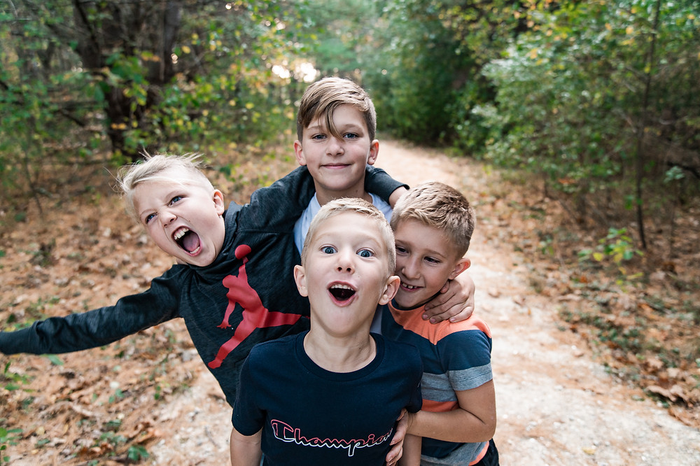four boys making silly faces and smiling for lifestyle family photo session wagon hill farm durham new hampshire