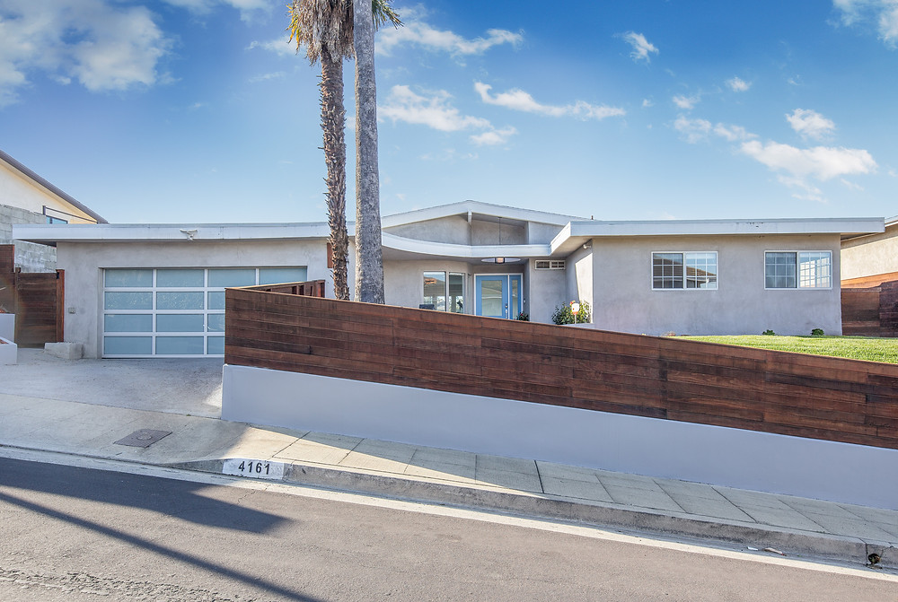 Modern home in Los Angeles Ca, with a wooden fence surrounding the home.
