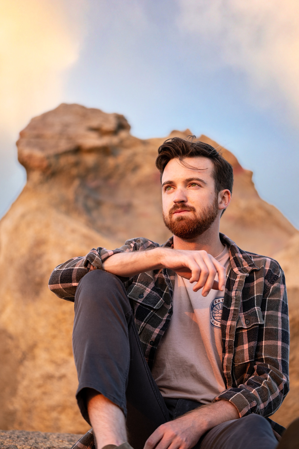 Young man sitting on a rock made of sandstone, gazing into the horizon during golden hour.