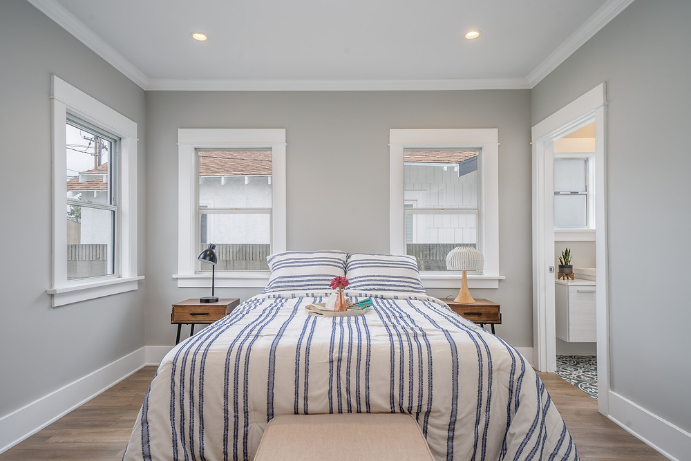 Queen sized bed in the middle of the room, with striped sheets