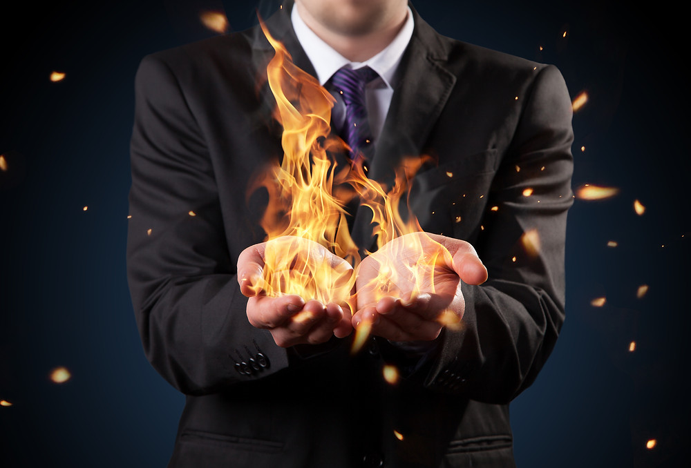 Businessman with fire in hands. Concept of threats and manager responsibility.jpg