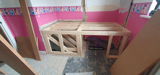 Building a bed frame above the staircase with storage space underneath
